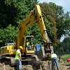 Workers using an excavator midday on Wednesday, August 6, did some stormwater drainage work along the north side of Wasserman Way, near that road's intersection with Mile Hill Road South at Fairfield Hills. Wasserman Way will be closed to through-traffic for about nine hours overnight on Sunday, August 10/Monday, August 11 so that workers can install a stormwater sewer line beneath the road there. (Gorosko photo)