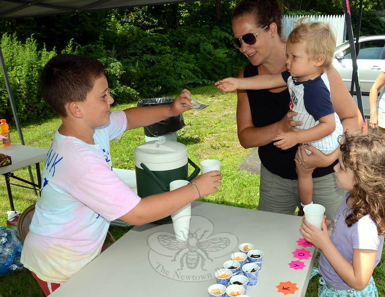 Eight-year-old Michael Poidomani wanted to do something to support the proposed Catherine Violet Hubbard Animal Sanctuary being established in memory of his late St Rose CCD classmate, so he set up a lemonade and juice stand along busy Route 25 at his grandfather's Town Line Auto Body August 3 to raise money for the effort. Among the many visitors to his stand were Beth Harrington and her children Kaitlyn and 2-year-old Carter, who appears to be covering the tab for his sister's refreshing beverage! (Voket photo)