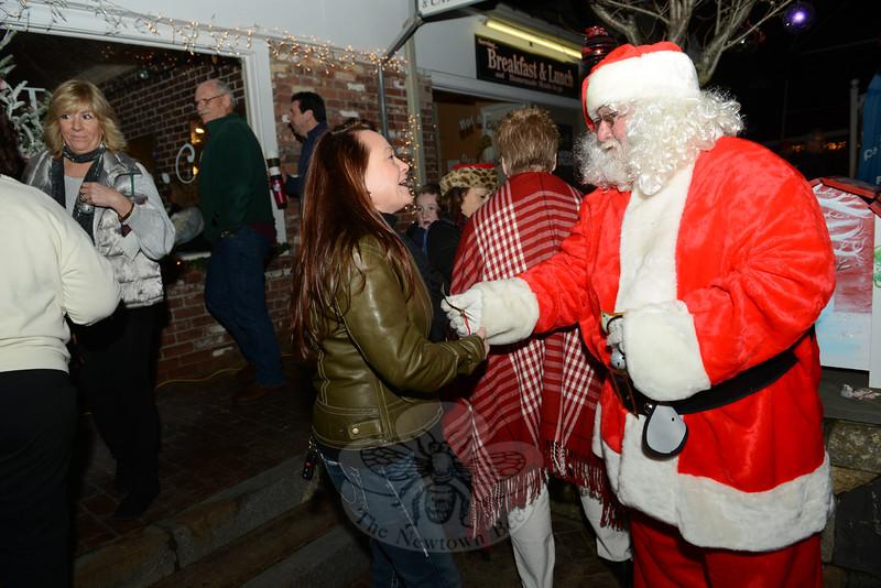 Dana Maceli smiles as Santa hands her a magical seasonal bell ornament. (Bobowick photo)