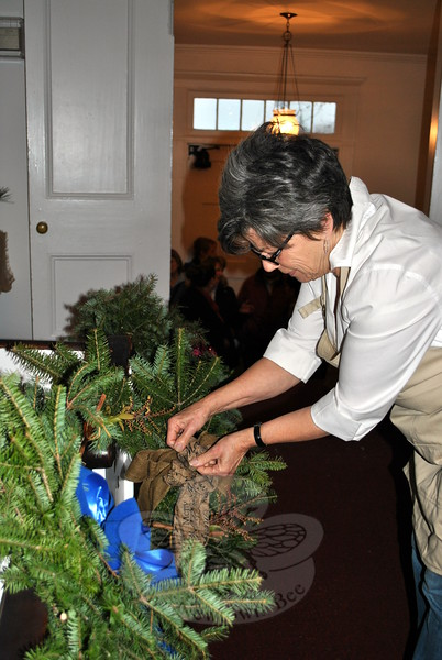 Garden Club member Vicky Taloni tweaks a bow on one of the dozens of hand decorated wreaths, just prior to the start of the Annual Greens Sale, Saturday, December 6, at The Meeting House on Main Street. The event draws a big crowd every year, and serves as a fundraiser for the local club. (Crevier photo)