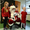 "Newtown Parks & Recreation hosted its annual Breakfast with Santa event at Newtown Middle School on Saturday, December 6. Craft tables were available, two therapy dogs attended, Mad Science of Stratford's ""Messy Mel"" Salguero and ""Mathematical Mike"" Elwell performed during the event, and a line of children was constantly waiting to visit with Santa. Adlien, left, baby Lars, and Evangeline Ekman posed with Santa when their turn came up. Brother Thorin did not pose for the photo but did attend the event too. Assistant Director of Recreation RoseAnn Reggiano said Bagel Delight, Masonicare Dining Services, DOrazio Sisters Bakery, Dunkin' Donuts Newtown, and Newtown Deli all contributed donations for the event. (Hallabeck photo)"