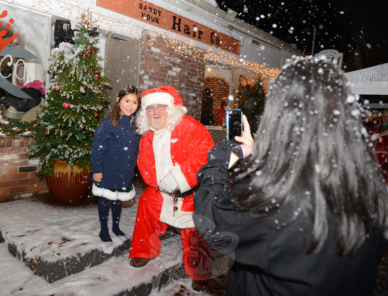 Brooke Heinen takes a picture of her daughter Sara and Santa as the three are covered in artificial snow. (Bobowick photo)