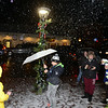 Artificial snow filled the sidewalk in Sandy Hook Center while residents ducked beneath umbrellas to keep out of the night's persistent rain. Abby Stites marches through both while under her M&M um-brella. (Bobowick photo)