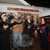 A small group of singers led guests through holiday carols Saturday, December 6. As the night's rain let up briefly, they were able to step out from under a tent also occupied by members of the Newtown High School Wind Ensemble. (Bobowick photo)