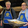 Rotary members Dan Honan, left, and Nick Borrello take a break from flipping flapjacks to rush a tray of hot pancakes to the serving window. (Crevier photo)