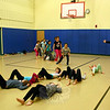 Sayer Mansfield, right, a Pilobolus dancer involved in the After School Arts Program at Reed, directs students through an exercise. One group of children were working their way across the gym floor on their backs, moving in one direction, while the second group stepped over them while traveling in the opposite direction. (Hicks photo)