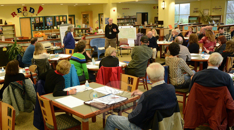 George Benson, town director of planning, standing at center, makes a point in the Reed Intermediate School library during a discussion on a proposal to modify the zoning regulations to allow rental apartments at the town-owned Fairfield Hills campus. About 50 people were at the Saturday, December 6, meeting, of whom about one-quarter were town officials. (Gorosko photo)