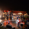 Wet streets glistened on Saturday, December 6, as a chilly rain soaked revelers at the annual Sandy Hook Village Holiday Tree Lighting. Dozens of umbrellas opened as small crowds gathered on side-walks, counting down from 10 until the trees — one with green and white lights and the other strung with traditional rainbow lights — lit the night. Adding to Sandy Hook Center's holiday appeal are newer lampposts wound with lights and strands of evergreen. Across the intersection is an old brick building now housing the Foundry Kitchen & Tavern, which is one of the many businesses where people ducked out of the rain until Sandy Hook Organization for Prosperity (SHOP) members were ready to light the trees.   (Bobowick photo)