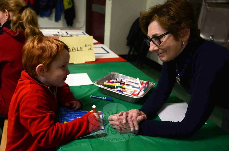 Martin Dunn, left, worked on coloring a quilt square for the new Comfort Quilt at Newtown Middle School on Saturday, December 6. Jan Brookes, right, one of the organizers for the project, offered him some advice. (Hallabeck photo)