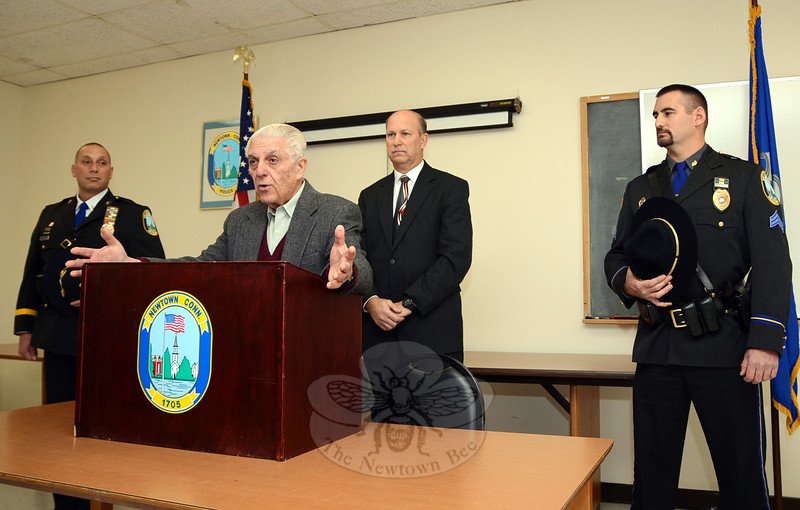 Police Commission Chairman Paul Mangiafico speaks to a gathering of colleagues, friends, family, and community members during a swearing-in ceremony for two of three recently promoted Newtown Police Department members. Chief Michael Kehoe was also on hand for the brief ceremony December 5 at Town Hall South honoring newly promoted Lieutenant David Kullgren, far left, and Sergeant Mat-thew Wood, far right. The Police Commission also authorized promoting Officer Scott Ruszczyk to the rank of sergeant. That promotion will become effective in May. (Voket photo)