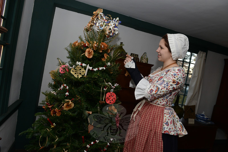 "Historical Society docent Mairin Hayes affixes decorations to a tree at the Matthew Curtiss House on Main Street Sunday, December 7. She and her mother Elin Hayes and grandmother Carole Fekete make the strands of popcorn and cranberries, dried apples, and decorations for the tree each year. Mairin's costume is ""perfectly authentic,"" she said. (Bobowick photo)"