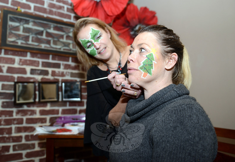 Danielle Fredericks adds a dash of paint to Amy Belval's cheek Saturday, making one more merry face in the crowd gathered for the Sandy Hook tree lighting. (Bobowick photo)