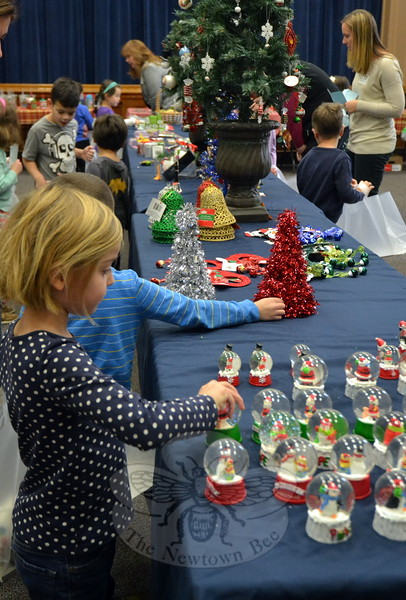 Hawley Elementary School kindergartener Morgan Kenny, standing front, was one of many students who looked through offerings at the school's Holiday Bazaar, run by the PTA, on Tuesday, December 8. (Hallabeck photo)