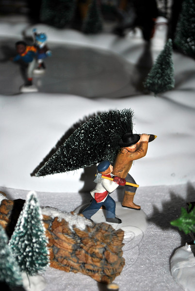"""Detailed characters carry a Christmas tree away from a tree farm, one of many """"neighborhoods"""" Mr Catalina has developed for his Department 56 Christmas Village. (Crevier photo)"""