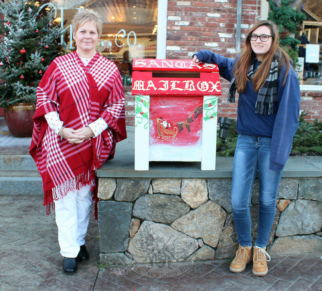 Sharon Doherty, left, and Noël Carbone stand with the Santa's Mailbox that was recently updated with colorful scenes by Noël. The high school sophomore responded to a request by Ms Doherty, a member of Sandy Hook Organization for Prosperity, to jazz up the mailbox before this year's Sandy Hook Tree Lighting. The box was put out in front of Sandy Hook Hair Co. and Sandy Hook Deli & Catering for the evening of December 5. It has been put into storage for safe-keeping, according to Ms Doherty, so that it can be used for future tree lightings. (Hicks photo)
