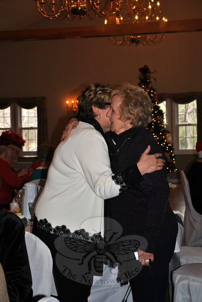 Newtown First Selectman Pat Llodra, right, gets a welcoming hug from Newtown Senior Center Director Marilyn Place, upon her arrival at the party. (Crevier photo)