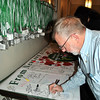 Gene Rosen of Sandy Hook signs a banner destined for San Bernardino, Calif., the site of a recent mass shooting. Mr Rosen was one of many who took time, following the interfaith service, to sign the banner.  (Crevier photo)