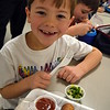 Middle Gate Elementary School kindergartener Ryan Mozelak smiled wide after trying a taste of the jimaca kale slaw served up by Chartwells Dining Services at his school on Thursday, December 10, as part of its Simply Good program. (Hallabeck photo)