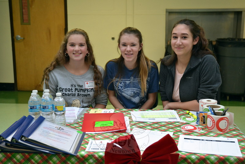 Newtown Middle School eighth graders, from left, Caroline Malin, Kateri Doty, and Justine Renjilian oversaw the registration booth for an American Red Cross blood drive and a simultaneous  food collection for FAITH Food Pantry in Sandy Hook at the middle school on Tuesday, December 8. (Hallabeck photo)