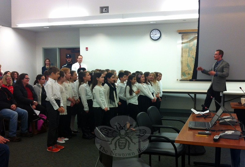 Hawley Elementary School music teacher Brian Kowalsky, right, led his third grade chorus members through singing for the Board of Education during its meeting on Tuesday, December 16. (Hallabeck photo)