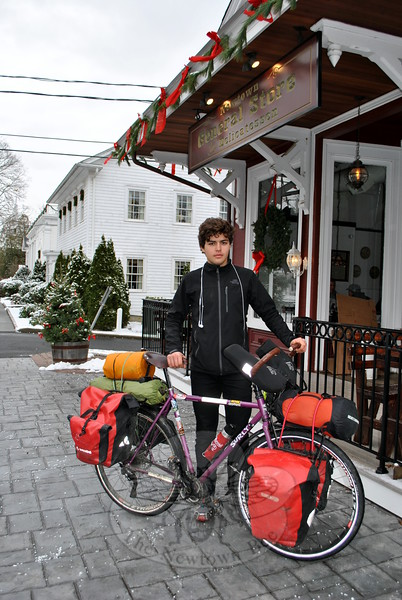 Eighteen-year-old Amaury Bargioni pauses in front of the Newtown General Store, Thursday, December 11. The young Parisian is biking around the world, and in passing through Newtown, was drawn to the historic building — the perfect lunch stop. (Crevier photo)