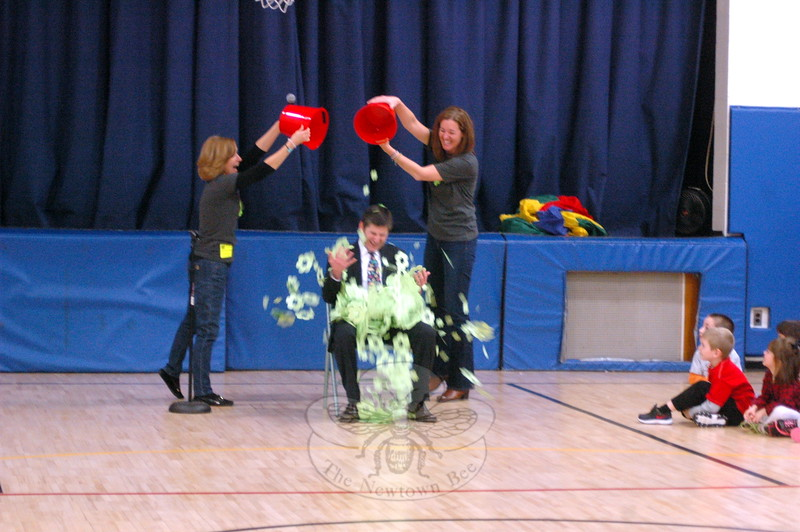 Middle Gate Elementary School Principal Chris Geissler, center, had paper Ben's Bells symbols dumped over him by Ben's Bells representatives Tricia Guiry, left, and Jennifer Avari, right, during a Community Circle assembly on Wednesday, December 10. (Hallabeck photo)