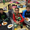 Middle Gate students, from left, Aidan England, Emily Brown, Nicholas DeBlasi, and Ryan Brown ate pizza before watching The Polar Express in the school's gymnasium for the school's annual holiday movie night hosted by the PTA. (Hallabeck photo)