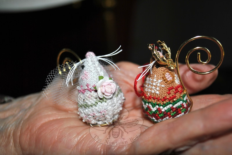 "Cupped in Peg Fobell's palm are Bride Mouse, with her scrap of a veil and pretty rose, and Reindeer Mouse, complete with antlers. The whiskers are the final touch added, says Mrs Forbell, and are what really give the petite creations ""personality."" (Crevier photo)"