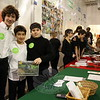 "Fraser Woods Montessori School eighth graders standing from left are Liam Byrne, Alessandro Orjuela, and Khal Bashawaty. The boys were working at a table with their fellow eighth graders on Thursday, December 17, to offer ""alternative gifts,"" for people to purchase at the school's annual Holiday Celebration. Each group of students worked to raise money for a different cause through Alternative Gifts International, and the boys worked to raise money for vegetable gardens in Tanzania. (Hallabeck photo)"