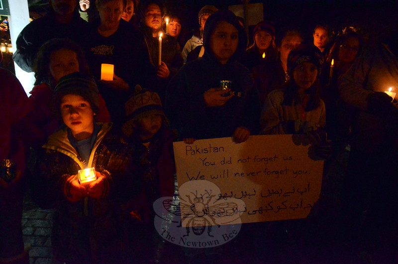 """After the shooting at Sandy Hook School, Elizabeth Vaughn, daughter of a Newtown Board of Educa-tion employee, saw a picture circulating from Karachi, Pakistan, with children lighting candles next to a sign that read, """"Connecticut school killing, [we] feel [your] pain as [you] would feel our pain."""" So when she learned about the devastating school attack in Peshawar, Ms Vaughn quietly organized a candle-light vigil that featured messages in Urdu translated onto posters by a Pakistani acquaintance. About two dozen friends and Sandy Hook Elementary School community members gathered for the brief memorial Friday, December 19, in Sandy Hook Center.  (Voket photo)"""