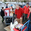 "The Frasier Woods School was buzzing with activity December 13 as Boy Scouts and leaders from Troop 370 at Newtown UMC joined residents and volunteers from The Newtown Fund either dropping off or delivering toys, gifts, and food to residents in need during the annual Depot Day event. Dozens of referrals through the town's Social Service Department or local clergy were gladly accepted by residents like Stacy White, pictured with volunteers loading a delivery for a mom and two teens her family ""adopted"" for the holidays. Scouts Matt Tassiello and Jacob Markowsky also assisted All-Star bus company staffer Joe Colangelo who was dropping off donations for two local families receiving holiday gifts and food collected by local bus drivers. (Voket photo)"