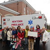 Representatives of the Newtown Volunteer Ambulance Corps (NVAC) joined Newtown VNA volunteers and supporters December 22 presenting a check to the local emergency responders in the amount of $25,000. Among those gathered for the occasion at the new ambulance headquarters are, from left, VNA officer Maureen McLachlan, NVAC Chief Michael Collins, Health District Director Donna Culbert, NVAC Trustee Bruce Herring, VNA officer Joan Reynolds, Maggie and Caroline Solloway with Molly the dog, VNA officers Rebeka Dahlgard, Anna Wiedemann, Mary Tietjen, NVAC Trustee Robert Grossman, MD, and VNA officers Alice Falkowitz, and Margareta Kotch. (Voket photo)