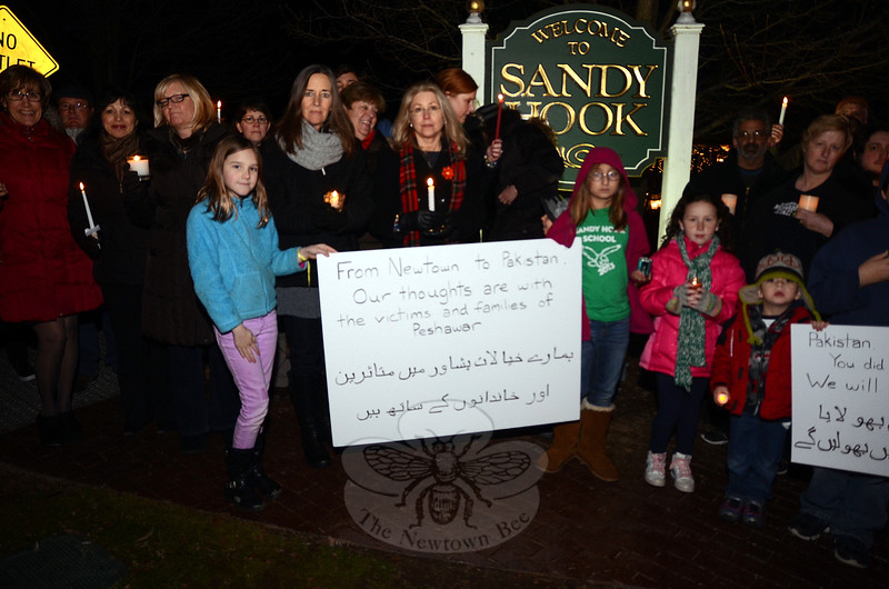 "After the shooting at Sandy Hook School, Elizabeth Vaughn, daughter of a Newtown Board of Educa-tion employee, saw a picture circulating from Karachi, Pakistan, with children lighting candles next to a sign that read, ""Connecticut school killing, [we] feel [your] pain as [you] would feel our pain."" So when she learned about the devastating school attack in Peshawar, Ms Vaughn quietly organized a candle-light vigil that featured messages in Urdu translated onto posters by a Pakistani acquaintance. About two dozen friends and Sandy Hook Elementary School community members gathered for the brief memorial Friday, December 19, in Sandy Hook Center.  (Voket photo)"