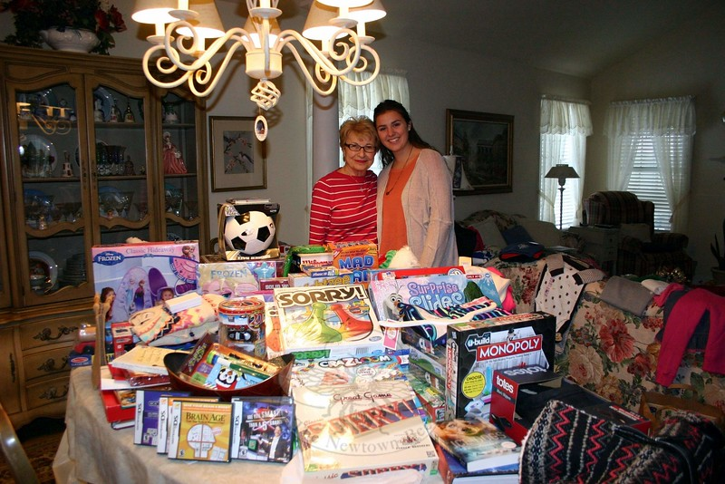 Since 2008, Sandy Hook resident Rosemary Trudell, left, with granddaughter Haley, has organized a collection of toys and children's clothing among the residents of Walnut Tree Village II. The collection is done for The Newtown Fund's Holiday Basket Program, which provides gifts and other items that will make lives brighter for some of Newtown's families in need. On December 11, Rosemary and Haley vis-ited residents of the condos on Walnut Tree Hill Road to collect items that were being donated. Spread out around them are many of the books, games, toys, warm clothing, athletic equipment, and gift cards that were donated this year. The Trudells then made sure everything was delivered to Fraser-Woods School for Depot Day, when donations from all groups, families, churches and businesses are all collected, sorted, and delivered to recipients. Depot Day was Saturday, December 13. (Hicks photo)