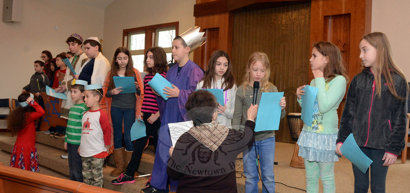 Dalia Coleman, the director of the Nezvesky School for Religious Education, foreground, holds a mi-crophone for a young student who performed at Congregation Adath Israel's annual Hanukkah program held on December 21 at the temple's sanctuary.  (Gorosko photo)