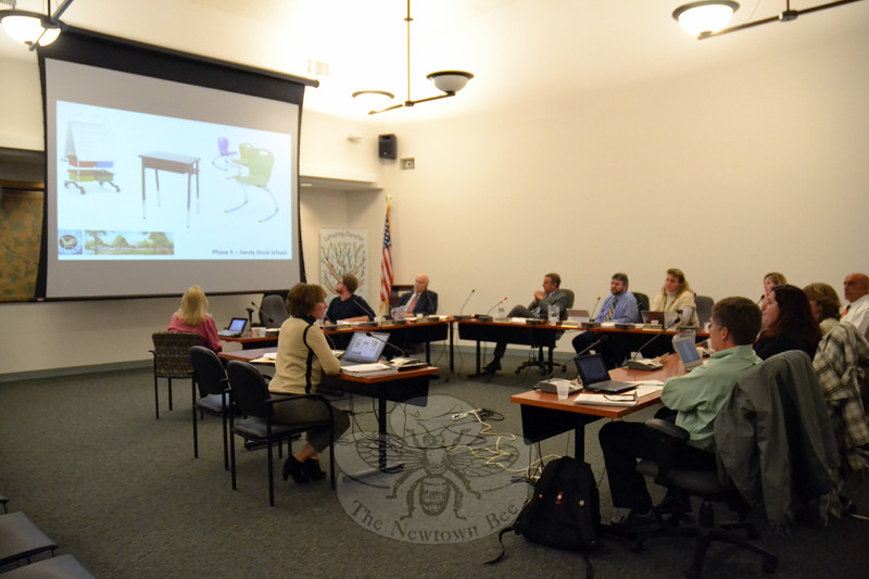 Diversified Project Management's Geralyn Hoerauf, seated left, presented furniture, shown on the projection screen, proposed in the fifth phase of the new Sandy Hook Elementary School building project to the Board of Education at its meeting on Tuesday, December 1. (Hallabeck photo)