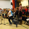 """While Hawley Elementary School music teacher Brian Kowalsky, left, led third and fourth graders through singing the song """"Mister Snowy Winter"""" during a concert assembly on Monday, November 31, school Principal Christopher Moretti, front, tossed cotton balls in the air like snow, which earned a number of laughs from the assembled students watching the performance. (Hallabeck photo)"""