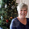 Glass artist Heidrun Morgan stands in front of a tree inside a seating area at Avancé Esthétiques, where guests have been enjoying displays of her creations recently. The tree behind her is laden with ornaments of Ms Morgan's creation.  The day spa, within Sand Hill Plaza at 228 South Main Street, will host an open house on Sunday afternoon. (Hicks photo)