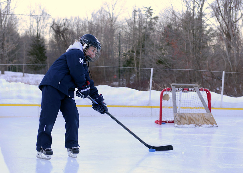 Earlier this month on a cold afternoon, Emma and Owen Hannah practiced their hockey maneuvers and skating skills at their home ice rink on Wendover Road. Their father Shaun Hannah built the skating space a few years ago.Emma, 8, plays hockey with Yale Youth Hockey, which Mr Hannah coaches. (Bobowick photo)