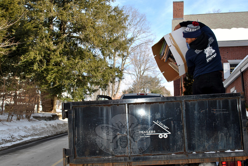 A worker with remediation specialist J.P. Maguire adds another box of water-damaged books to a trailer filled with thousands more ruined books from the Children's Department of the C.H. Booth Library, where a February 17 pipe break sent water throughout that space. The books, located directly beneath the break, are not salvageable. (Crevier photo)