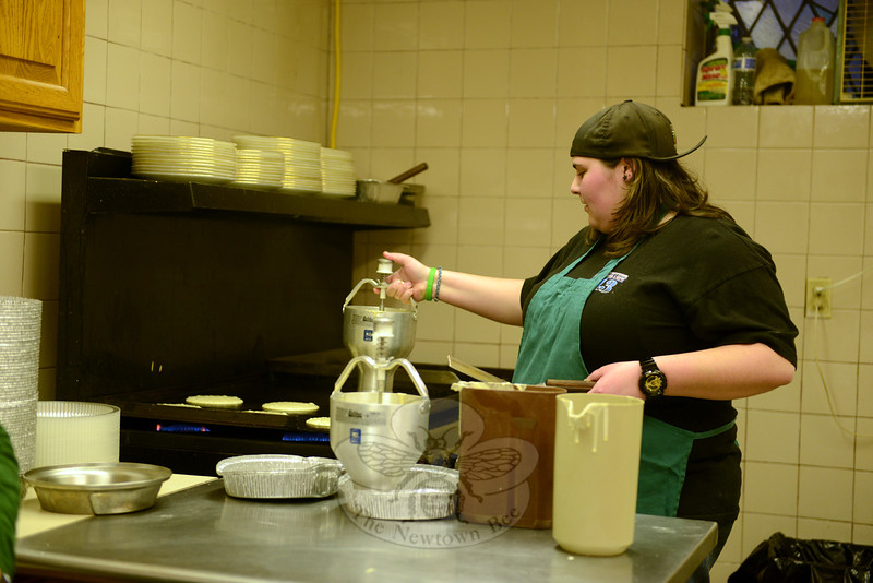 Erica Knapp pours out perfectly measured amounts of pancake batter onto a hot surface as diners arrive for supper Tuesday night at the St John's Episcopal Church Hall for the annual Shrove Tuesday Pancake Supper. Around them are tables beginning to fill shortly after 5 pm. (Bobowick photo)