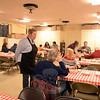 Mary Fellows speaks with guests Tuesday as they wait for their plates of fresh pancakes and hash at the St John's Episcopal Church Hall for the annual Shrove Tuesday Pancake Supper. Around them are tables beginning to fill shortly after 5 pm. (Bobowick photo)