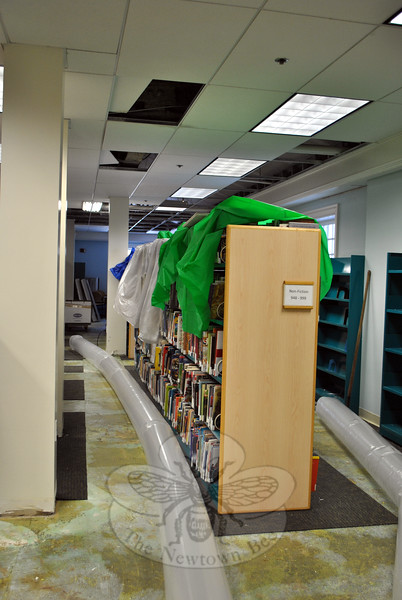 In a scene all too reminiscent of January 2014, plastic pipes snake through the Children's Department of the C.H. Booth Library, removing book-damaging moisture from the air. Missing ceiling tiles mark the area most heavily affected by broken sprinkler system pipes. (Crevier photo)