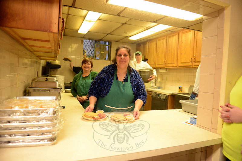 Filled with fresh, hot buttered pancakes, homemade hash, and applesauce, are dinners ready for guests Tuesday evening during the annual pancake supper. Janet Knapp works with Lisa Ryan, left, Bruce Moulthrop, right, and in the background, her daughter Erica, who pours and flips cakes on the griddle. (Bobowick photo)