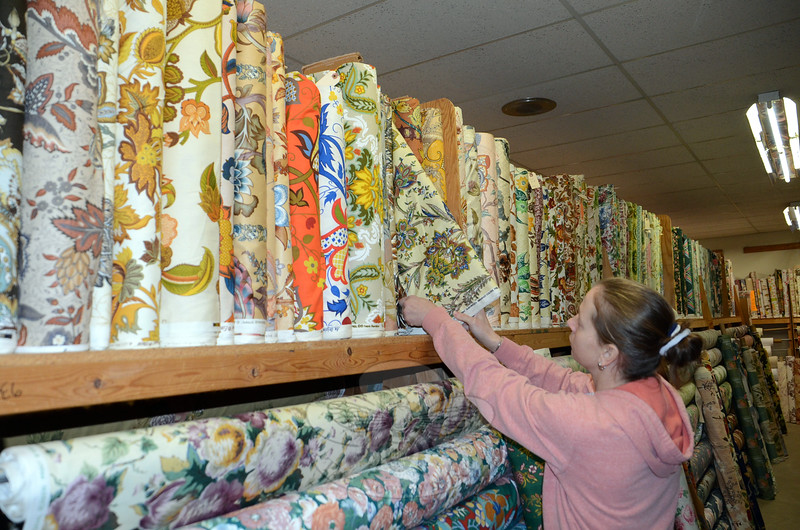 Chintz-N-Prints owner Laura Gardner pulls a bolt of vintage fabric that has been residing at her South Main Street store since before she was born. Her grandparents opened the shop in 1957 and acquired a number of fabrics that are still available on the racks, making the shop a destination for film and television designers looking for authentic period patterns and textures to dress their sets. (Voket photo)