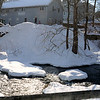 Spending time playing outdoors Sunday and spied from across the Pootatuck River in Sandy Hook Center were two young girls climbing mounded snow. They scrambled atop piles of plowed snow and looked across a parking lot shared by several storefronts and Sandy Hook Baptist Church. (Bobowick photo)