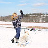 Riley Trask, 10, tosses a snowball that his eager small yellow Lab chases downhill. Below, standing near some dog agility equipment is Riley's twin sister Dylann. The girls and a variety of dogs at Newtown Park and Bark enjoyed a day of sunshine and nearly 40-degree temperatures — a heat wave compared to the negative numbers from just a few nights earlier. (Bobowick photo)
