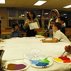 Susan Rosano, center, an artist with Arts for Learning Connecticut who recently moved to Vermont, led a group of Middle Gate Elementary School community members on Tuesday, February 10, through the first steps of completing one of the murals that will eventually decorate the school's cafeteria. (Hallabeck photo)
