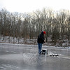 """Former New Fairfield resident who has called Newtown home since August, James Marino had the pond and the mid-January sunset to himself Wednesday afternoon. With light supplies of a hand drill to cut a hole through the ice, a small pole and a pail, he stood at the center of Warner Pond on Old Mill Road off of Route 34, surrounded only by frigid trees. Just past 4 pm as fading orange sunlight slipped through the trees, Mr Marino watched for movement on his line. He had some earlier luck and caught two """"miniscule""""fish. A mason by trade, he is often able to find time to fish this time of year, he said. (Bobowick photo)"""