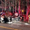Sandy Hook firefighters wait for a wrecker to arrive after responding to an accident in the area of 118 Berkshire Road during the early morning hours of last Friday morning. Police report that motorist Robert Vogt, 26, of Northford was driving a 2012 Honda CR-V SUV eastward on Berkshire Road, just east of its intersection with Zoar Road, at about 3:30 am on January 8, when while negotiating a curve in the road, the SUV entered the opposite lane and then went off the road, sideswiping a stone wall and then rolling over, landing on its roof in the eastbound lane. Vogt was able to self-extricate from the vehicle, and did not report injuries. Newtown Volunteer Ambulance Corps also responded to the accident. Police said they issued Vogt a misdemeanor summons for driving with a suspended license and for failure to keep to the right on a curve. (Hicks photo)